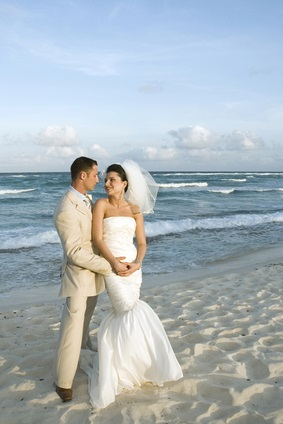 newlyweds on beach by ocean
