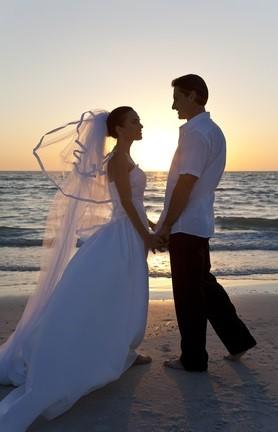 newlyweds on beach at sunset