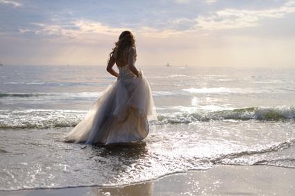 bride standing at ocean shore